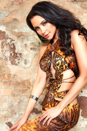 animal sexy: Beautiful sexy young brunette woman with long black hair and evening makeup in long dress wild animal print fashion style party in black and white colors smiling sexy and hot