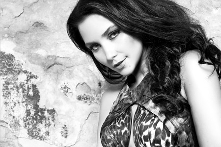 Beautiful sexy young brunette woman with long black hair and evening makeup in long dress wild animal print fashion style party in black and white colors smiling sexy and hot photo