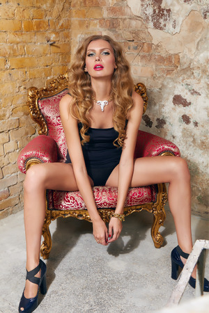 Beautiful sexy woman long blonde hair in black t-shorts and high heel sitting on the red armchair in the corner near brick wall background makeup fashion style photo