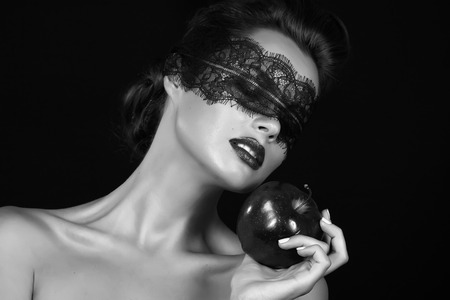 apple bite: Beautiful young girl witch sorceress with a bandage black lace holding ripe apple magic witchcraft tempted to bite tale Sleeping Beauty Halloween