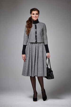 Beautiful young business woman with evening make-up wearing a skirt to the knee wool coat jacket high high heels and a small black handbag, business clothes for meetings and walks autumn collection photo