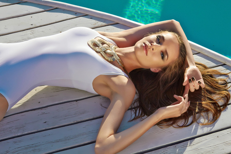 Beautiful blonde girl in good shape with long light hair and tan perfect skin in white swimming suite with golden jewelry with lie near the pool with green water keeping open her eyes with soft smile Фото со стока