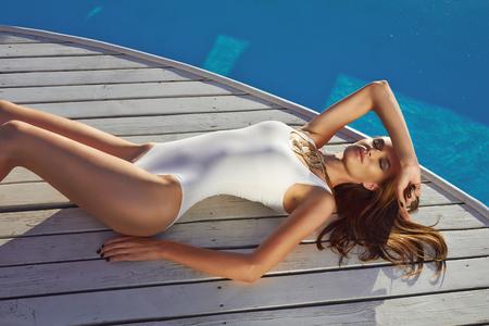 traje de bano: Hermosa chica rubia en buena forma con la luz de pelo largo y piel bronceado perfecto en la habitaci�n blanca nataci�n con joyer�a de oro con mentira cerca de la piscina con el mantenimiento de agua verde abri� los ojos con una sonrisa suave