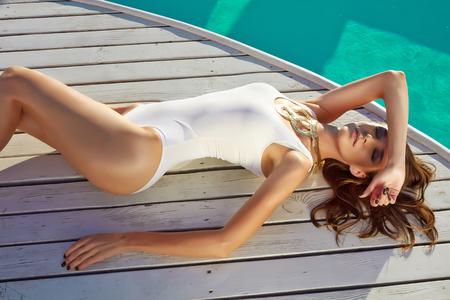 perfect waves: Beautiful blonde girl in good shape with long light hair and tan perfect skin in white swimming suite with golden jewelry with lie near the pool with green water keeping open her eyes with soft smile Stock Photo