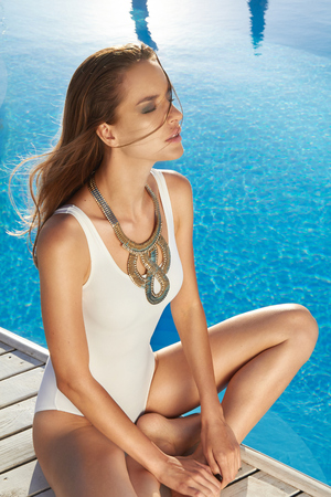 body jewelry: Beautiful blonde girl in good shape with long light hair and tan perfect skin in white swimming suite with golden jewelry with lie near the pool with green water keeping open her eyes with soft smile Stock Photo