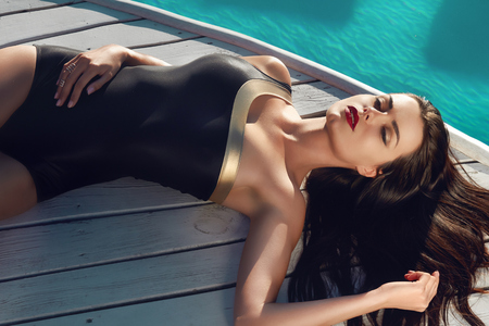 black and blue: Beautiful sexy young woman with perfect slim figure with long dark hair and wet bathing suit fashion in stylish swimmwear from the sun is sunning by swimming pool swim, sunbathe have fun at beach party Stock Photo