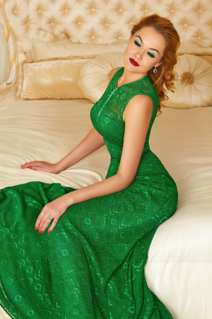 Beautiful young red-haired curly woman with bright makeup crimson lipstick wearing a long bright designer evening dress, green earrings with emerald diamonds sitting on bed in  bedroom interior photo