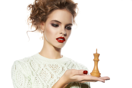 Beautiful young girl with a bright evening make-up, orange, scarlet lipstick, rosy cheeks, eye shadow, nail polish, blonde curly hair dressed in winter white knitted sweater holding a king chess piece