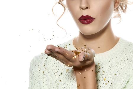 물결 모양의 머리 밝은 저녁 메이크업 빨간 입술 긴 털이 속눈썹을 가진 아름 다운 섹시 한 금발 소녀가 그의 앞에 골드 장식 조각 손바닥을 보유하고