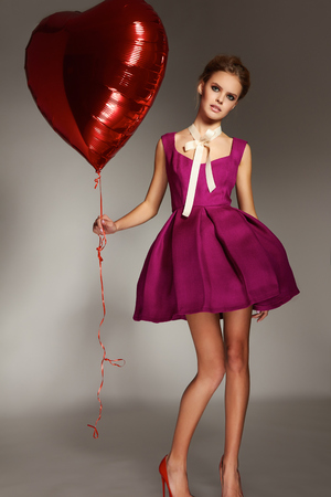 dress form: Beautiful sexy young girl blonde hair gathered in a bun, evening natural makeup wearing a bright pink short evening dress and elegant high heels holding a big red balloon in the form of hearts, Valentines Day.