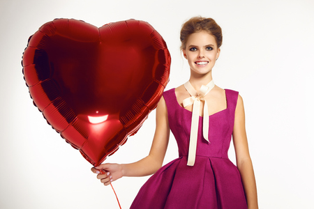 sexy young girl: Beautiful sexy young girl blonde hair gathered in a bun, evening natural makeup wearing a bright pink short evening dress and elegant high heels holding a big red balloon in the form of hearts, Valentines Day.