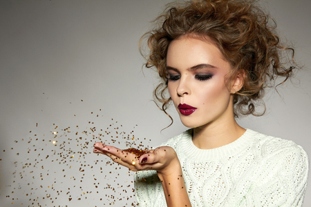 Beautiful young blond girl with wavy hair bright evening make-up red lips long fluffy eyelashes holds palm with gold sequins in front of him and blows them a holiday New Year Christmas joy fun