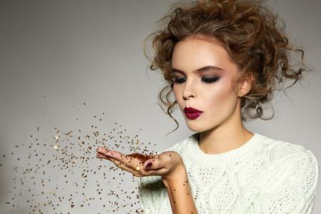 Schönes reizvolles junges blondes Mädchen mit gewellten Haare hell Abend Make-up roten Lippen lange flauschige Wimpern hält Palme mit goldenen Pailletten vor ihm und bläst sie einen Urlaub Neujahr Weihnachten Freude fun Standard-Bild