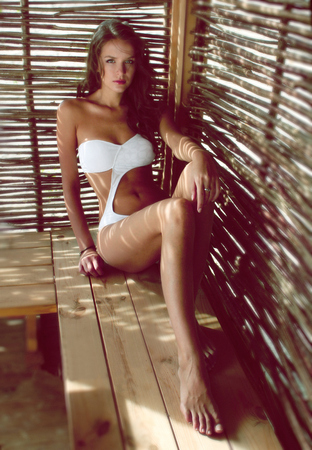 Beautiful sexy young blond woman with curly long hair and soft natural make-up wearing a white designer swimsuit sitting in an arbor of vines beach shadow gaps on the beach beach party photo