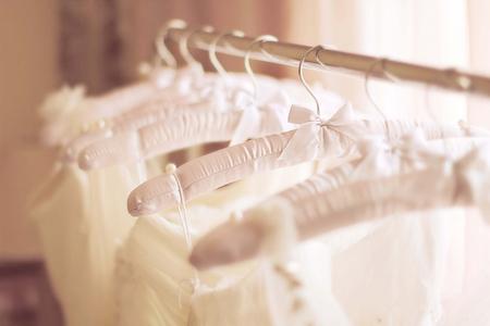 wesele: Piękne białe suknie ślubne wykonane z krem szyfonu, jedwabiu, tiulu i koronki wiszące na wieszakach z kokardkami