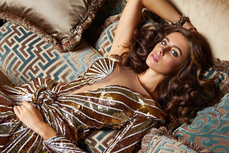 Beautiful sexy brunette woman with wavy hair in a bright colored suit on the wide shoulder straps with rings bracelets accessories, or evening hairstyle and makeup sitting in chair with cushions