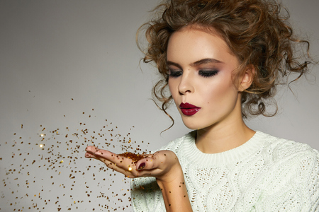 Mooie sexy jonge blonde meisje met golvend haar heldere avond make-up rode lippen lange pluizige wimpers houdt palm met gouden pailletten voor hem en blaast ze een vakantie Nieuwjaar Kerstmis vreugde leuk Stockfoto - 33920857