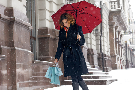 warm jacket: Beautiful sexy young woman with curly brown hair with bright makeup wearing a black coat walking on snow-covered streets past shops with red umbrella and gift packs for Christmas and New Year Winter Stock Photo