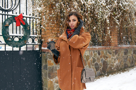 Beautiful sexy young woman with curly brown hair with bright makeup wearing a brown coat goes on snow-covered street past the shops with a cup of hot coffee, cappuccino, tea, Christmas and New Year Winter photo
