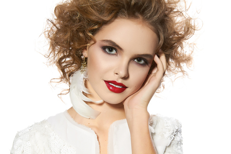 blonde curly hair: Portrait of beautiful young girl with a bright evening make-up perfect skin and blue eyes, red lips, nice smile blonde curly hair dressed in a white jacket with sequins on a white background in studio Stock Photo