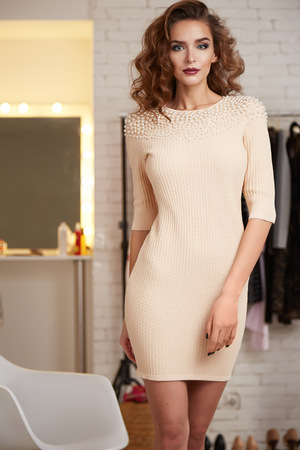 chic woman: Beautiful sexy young woman with curly brown hair bright evening make-up wearing a short cocktail dress cream colored pearls perfect body shape sports a healthy diet, chic luxury of  interior at party Stock Photo