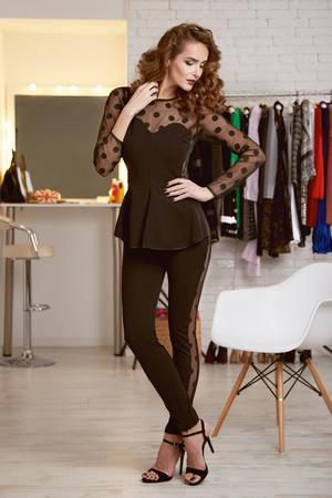 body shape: Bella sexy ragazza con i capelli ricci biondi e sera luminoso make-up che indossa un abito di seta nera alla moda fotografato all'interno di un negozio di abbigliamento corpo sottile forma dieta elegante alla festa Archivio Fotografico