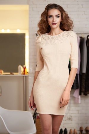 chic woman: ?Beautiful sexy young woman with curly brown hair bright evening make-up wearing a short cocktail dress cream colored pearls perfect body shape sports a healthy diet, chic luxury of  interior at party