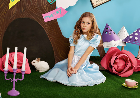 wavy hair: Little beautiful girl with long wavy hair in a blue silk dress in the scenery of Alice in Wonderland with white fluffy bunny cartoon fairy tale adventure Stock Photo