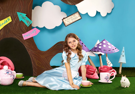 hollyday: Little beautiful girl with long wavy hair in a blue silk dress in the scenery of Alice in Wonderland with white fluffy bunny cartoon fairy tale adventure Stock Photo