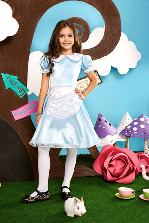 Little beautiful girl with long wavy hair in a blue silk dress in the scenery of Alice in Wonderland with white fluffy bunny cartoon fairy tale adventure Stock Photo