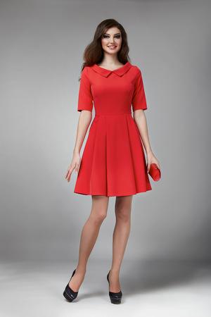完璧な夏日焼け薄い図を色の短いドレスとハイヒールの靴小さいサイズのハンドバッグを持って着た明るい夜メイク長いウェーブのかかったブロン