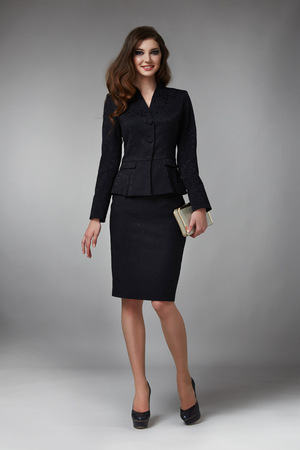 skirt suit: Beautiful young business woman with evening make-up wearing a skirt to the knee and a silk blouse with lace long sleeves and high-heeled shoes and a small black handbag, business clothes for meetings