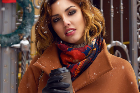 Beautiful sexy young woman with curly brown hair with bright makeup wearing brown coat goes on snow-covered street past shops with a cup of hot coffee, cappuccino, tea, Christmas and New Year Winter photo