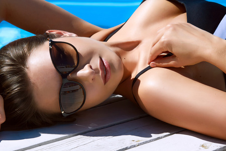 Beautiful sexy young woman with perfect slim figure with long dark hair and wet bathing suit fashion in stylish glasses from the sun is sunning by swimming pool swim, sunbathe have fun at beach party Stock Photo