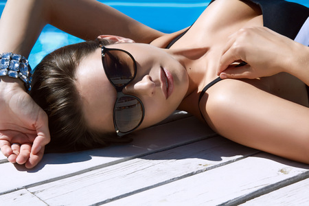 swimming suit: Beautiful sexy young woman with perfect slim figure with long dark hair and wet bathing suit fashion in stylish glasses from the sun is sunning by swimming pool swim, sunbathe have fun at beach party Stock Photo
