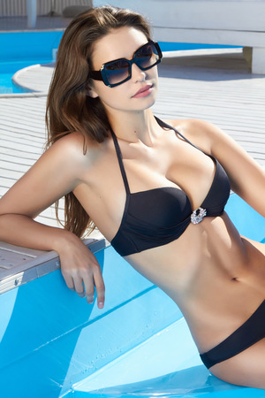 wet suit: Beautiful sexy young girl with perfect slim figure with long wet hair and bathing suit in fashionable stylish sun glasses sitting on the steps of swimming pool swim, sunbathe, have fun at beach party Stock Photo