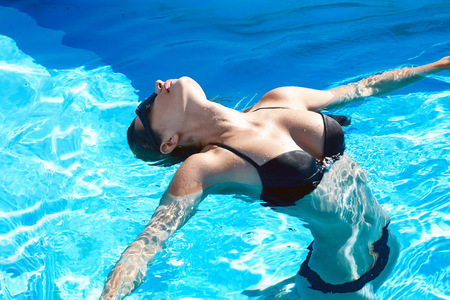 Beautiful sexy young girl with perfect slim figure with long wet hair and bathing suit in fashionable stylish sun glasses sitting on the steps of swimming pool swim, sunbathe, have fun at beach party photo