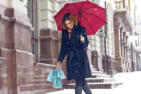 クリスマスと新しい年の冬は赤い傘とギフト パックお店過去の雪に覆われた街を歩いて黒いコートを着て明るいメイクと巻き毛の茶色の髪と美しい