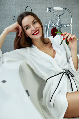 be wet: Beautiful young sexy woman with dark hair, evening make-up, red lips and manicure sitting in the bathroom in a white silk robe, holding a red rose smiling white teeth, Valentines Day Stock Photo