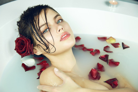 be wet: Beautiful young sexy woman with dark hair wet, evening makeup, takes bath with milk and rose petals and candles, beauty salon and spa Valentines Day