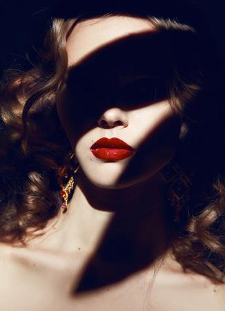 Schöne junge sexy blonde Mädchen mit dem lockigen Haar mit hellen Make-up rote Lippen, roter Lippenstift, lange Ohrringe in dunkle Schatten Standard-Bild - 35772779