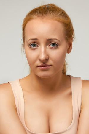 decepci�n: Retrato de una muchacha rubia joven hermosa con el pelo largo recogido en una belleza natural maquillaje natural coleta expresa la emoci�n de la tristeza, el dolor, la decepci�n