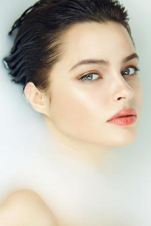 Belle jeune fille sexy aux cheveux noirs mouillée, maquillage de soirée, prend un bain de lait avec une peau parfaite dans une atmosphère romantique, un salon de beauté et un spa pour femme à la Saint-Valentin
