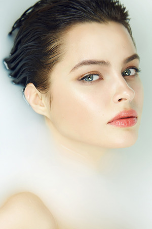 puro: Muchacha atractiva joven hermosa con el pelo oscuro mojado, maquillaje de noche, tiene baño con leche piel bronceado perfecto en un ambiente romántico, salón de belleza estética y spa para la mujer en el Día de San Valentín