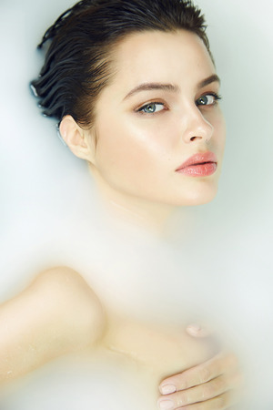 Beautiful young sexy girl with dark hair wet, evening makeup, takes bath with milk tan perfect skin in romantic atmosphere, beauty cosmetic salon and spa for woman at Valentines Day