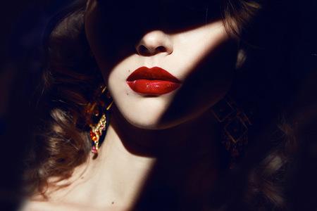 sexy young girl: Крупным планом лицо принадлежит к красивой молодой секси блондинка девушка с вьющиеся волосы чистой белоснежной кожей и яркий макияж красные губы, красные помады, длинные серьги в темных теней пальмовых листьев