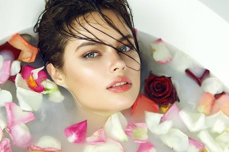 美しい若いセクシーな黒髪の女の子濡れて、夜の化粧、ロマンチックな雰囲気、美容化粧品、女性用スパで日焼けの完璧な farfor ゆば入りはバレンタ 写真素材