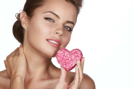 woman eating cake: Beautiful sexy brunette woman eating cake shape of heart on a white background, healthy food, tasty, organic, romantic valentines day