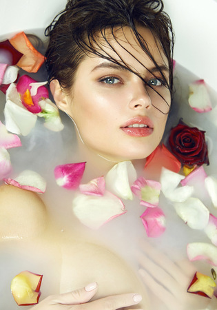 be wet: Beautiful young sexy girl with dark hair wet, evening makeup, takes bath with milk tan perfect farfor skin in romantic atmosphere, beauty cosmetic salon and spa for woman at Valentines Day