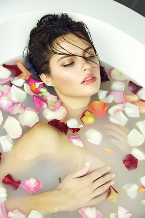 sexy bath: Beautiful young sexy girl with dark hair wet, evening makeup, takes bath with milk tan perfect farfor skin in romantic atmosphere, beauty cosmetic salon and spa for woman at Valentines Day. Stock Photo